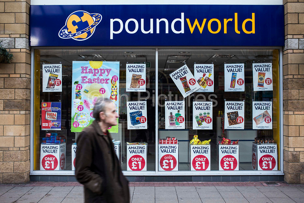 An old British man walks past a £1 pound world shop in Middlesborough town centre, North Yorkshire, United Kingdom. There has been a dramatic increase in the number of pound shops across Britain, especially in poor and deprived areas.  All stock is priced one pound and offers amazing value.