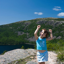 A young girl (age 4) celebrates iking to the summit of South Bubble Mountain in Maine's Acadia National Park.