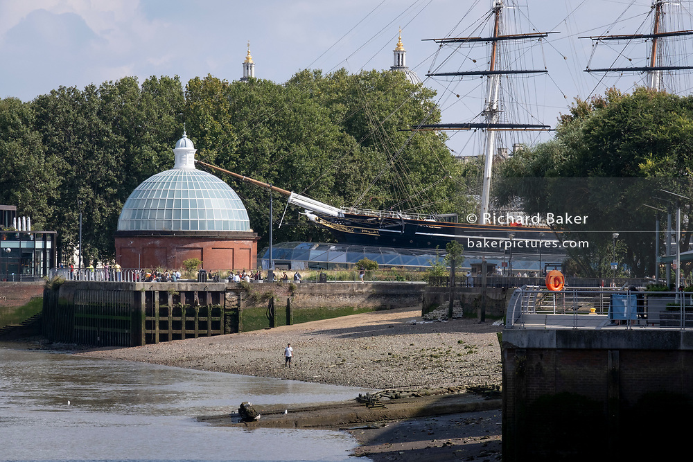 A man walks along the Thames foreshore near the Cutty Sark cargo clipper whose tall masts are seen near the southern entrance of the Greenwich Foot Tunnel and the twin domes of Greenwich Hospital, on 16th September 2021, in London, England.