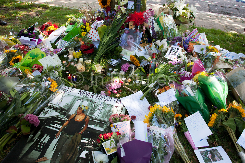 People gather and lay flowers at a memorial opposite the home of Amy Winehouse, Camden Square, North London. It was announced that the tragic singer had died on 23rd July 2011. The music world has been paying tribute to singer Amy Winehouse, 27, who was found dead at her London home following years of drug and alcohol abuse largely attributed to her troubled character and fame.