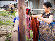 05 SEPTEMBER 2013 - BANGKOK, THAILAND:  A Cambodian woman hangs her laundry to dry next to the corrugated metal dormitory that is worker housing at the construction site of a new high rise apartment / condominium building on Soi 22 Sukhumvit Rd in Bangkok. The workers live in the corrugated metal dorms on the site. Most of the workers at the site are Cambodian immigrants.             PHOTO BY JACK KURTZ
