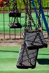 Sheffield South Yorkshire - Childrens swings in Hillsborough park playground are fastened together to stop them from being used as part of the social distancing rules brought in under the UK Emergency measures<br /> <br /> 15 April 2020<br /> <br /> www.pauldaviddrabble.co.uk<br /> All Images Copyright Paul David Drabble - <br /> All rights Reserved - <br /> Moral Rights Asserted -