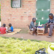 CAPTION: Catherine Anaso and her family having lunch together. In this culture, the father sits together with his first-born son, while the rest of the children eat to one side with their mother. LOCATION: Apapai Parish, Otuboi Sub-county, Kalaki County, Kaberamaido District, Uganda. INDIVIDUAL(S) PHOTOGRAPHED: From left to right: Catherine Anaso, Cecilia Acwichi, Nancy Acen, Daniel Owange, Innocent Jacob Okot and David Alele.
