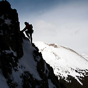 Ben Marshall works his way up a new route on McClellan Mountain in Colorado. Mount Kelso rises behind.