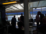 Silhouetted people onboard a ferry at Sami, Cephalonia, Greece