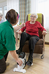Nurse with senior woman exercising on exercise bike in rest home