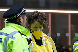 © Licensed to London News Pictures. 14/10/2019. London, UK. An Extinction Rebellion protester dressed as a canary talks to a Police Officer after being removed from The Walkie Talkie building . Protesters are today targeting the financial district.  Photo credit: George Cracknell Wright/LNP