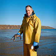 Portrait of Julian, a Filey fisherman holding a lobster which he has just caught on his coble (boat), Filey, North Yorkshire, UK