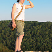 Man protecting eyes from sun with hand on top of Zhiguli mountains
