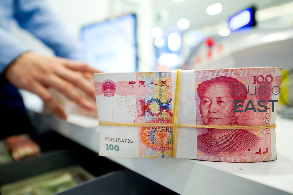 SHANGHAI, CHINA - MAY 13: An employee stacks Chinese Yuan bank notes in a Standard Chartered bank branch, on May 13, 2015, in Shanghai, China. Aiming for more access to the global financial market, China is encouraging the RMB or Renminbi as the Chinese Yuan is known in China (meaning 'the money of the people') to become more global. (Photo by Servais Mont/Getty Images)