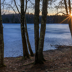 First light on the frozen Bellamy Reservoir in Madbury, New Hampshire.