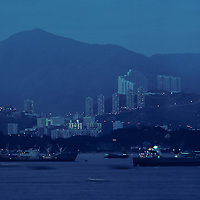 China, Hong Kong, Cargo ships sails past Kowloon Peninsula in Hong Kong Harbour