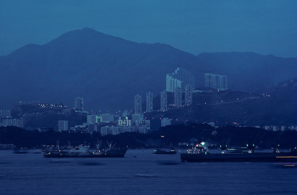 China, Hong Kong, Cargo ships sails past Kowloon Peninsula in Hong Kong Harbour