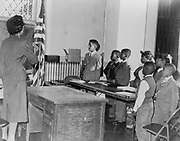 Mrs Claire Cumberbatch, of 1303 Dean Street, leader of the Bedford-Stuyvesant group protesting alleged 'segregated' school, leads the  oath of allegiance to the flag in a class of African Americans, 12 September 1958. Photographer: Dick DeMarsico.