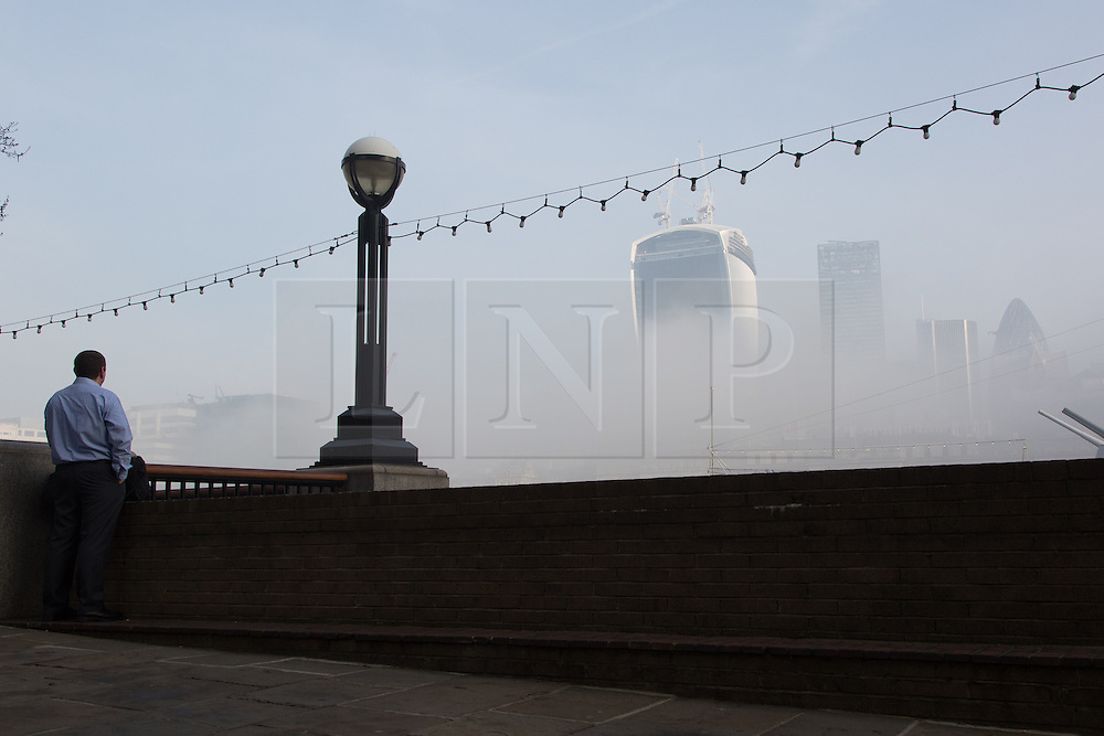 © Licensed to London News Pictures. 13/03/2014. London, UK. A man watches as thick fog begins to lift in morning sunlight over the 'Walkie Talkie' skyscraper in London on 13th March 2014. Photo credit : Vickie Flores/LNP