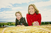 Mom and son pose for portrait on haystack.