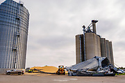 "12 AUGUST 2020 - SLATER, IOWA: Grain silos at the Heartland Cooperative in Slater were destroyed during the storm Monday. According to Iowa Governor Kim Reynolds, the storm damaged 10 million acres of corn and soybeans in Iowa, about 1 one-third of Iowa's 32 million acres of agricultural land. Justin Glisan, Iowa's state meteorologist, said the storm Monday, Aug. 10, lasted 14 hours and traveled 770 miles through the Midwest before losing strength in Ohio. The storm was a seldom seen ""derecho"" that packed straight line winds of nearly 100MPH. The storm pummelled Midwestern states from Nebraska to Ohio.    PHOTO BY JACK KURTZ"