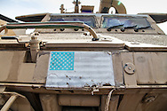 Humvee on a base in Baghdad, Iraq with a faded a American flag.