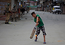 July 13, 2017 - India - A boy plays a shot as Indian paramilitary soldiers stand alert  in curfewed old city Srinagar the summer capital of Indian controlled Kashmir.Government imposed strict curfew in many parts of Srinagar following the martys day and killing of three rebels in central Kashmir's Budgam on Tuesday July 11, 2017. (Credit Image: © Faisal Khan/Pacific Press via ZUMA Wire)