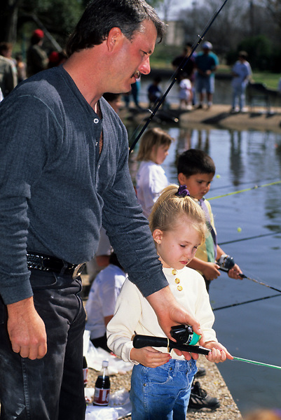 Stock photo of a man teaching his daughter to fish with other children at a small pond