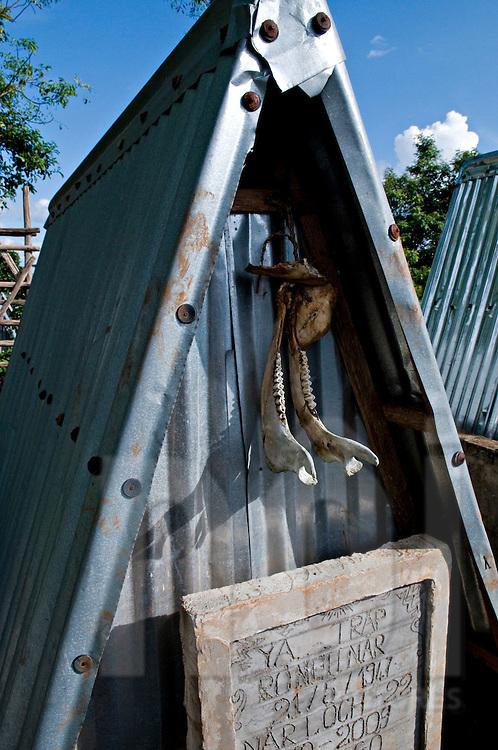 An animal jowbones hangs outside of a Bahnar ethnic gravestone. Pleiku area, Vietnam, Asia