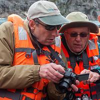 Tourists take pictures from a zodiac raft in Seno Chico, a fjord in Alberto de Agostini National Park, Tierra del Fuego, Chile.