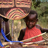 Africa, Kenya, Maasai Mara. Young Maasai boy peeks out at boma market.