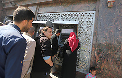 April 5, 2017 - Gaza City, Gaza Strip, Palestinian Territory - Palestinian employees paid by the Palestinian Authority wait to receive their salaries from an ATM, outside a Bank in Gaza City April 5, 2017. The salaries of Palestinian employees in Gaza strip have been reduced by about 30  (Credit Image: © Mohammed Asad/APA Images via ZUMA Wire)