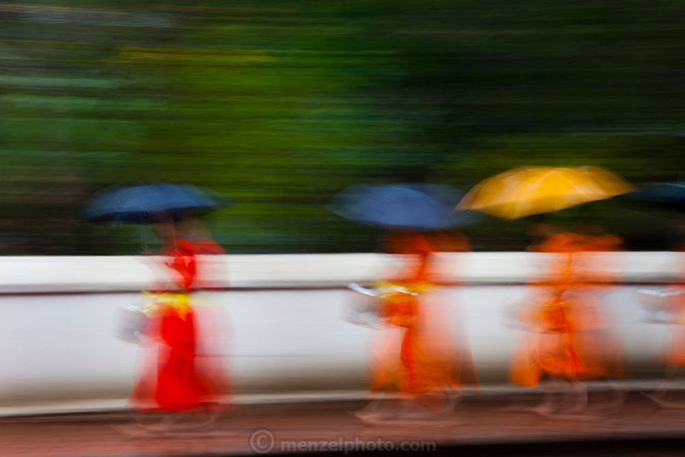 Luang Prabang, Laos. Every morning at dawn, Buddhist monks walk down the streets collecting food alms from devout, kneeling Buddhists, and some tourists. They then return to their temples, or wats, and eat together. This procession is called Tak Bat, or Making Merit.