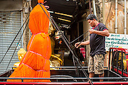 "12 NOVEMBER 2012 - BANGKOK, THAILAND:   A truck driver secures a statue of the Buddha to his truck on Bamrung Muang Street in Bangkok. Buddhas are covered in saffron when they are moved. Thanon Bamrung Muang (Thanon is Thai for Road or Street) is Bangkok's ""Street of Many Buddhas."" Like many ancient cities, Bangkok was once a city of artisan's neighborhoods and Bamrung Muang Road, near Bangkok's present day city hall, was once the street where all the country's Buddha statues were made. Now they made in factories on the edge of Bangkok, but Bamrung Muang Road is still where the statues are sold. Once an elephant trail, it was one of the first streets paved in Bangkok. It is the largest center of Buddhist supplies in Thailand. Not just statues but also monk's robes, candles, alms bowls, and pre-configured alms baskets are for sale along both sides of the street.    PHOTO BY JACK KURTZ"