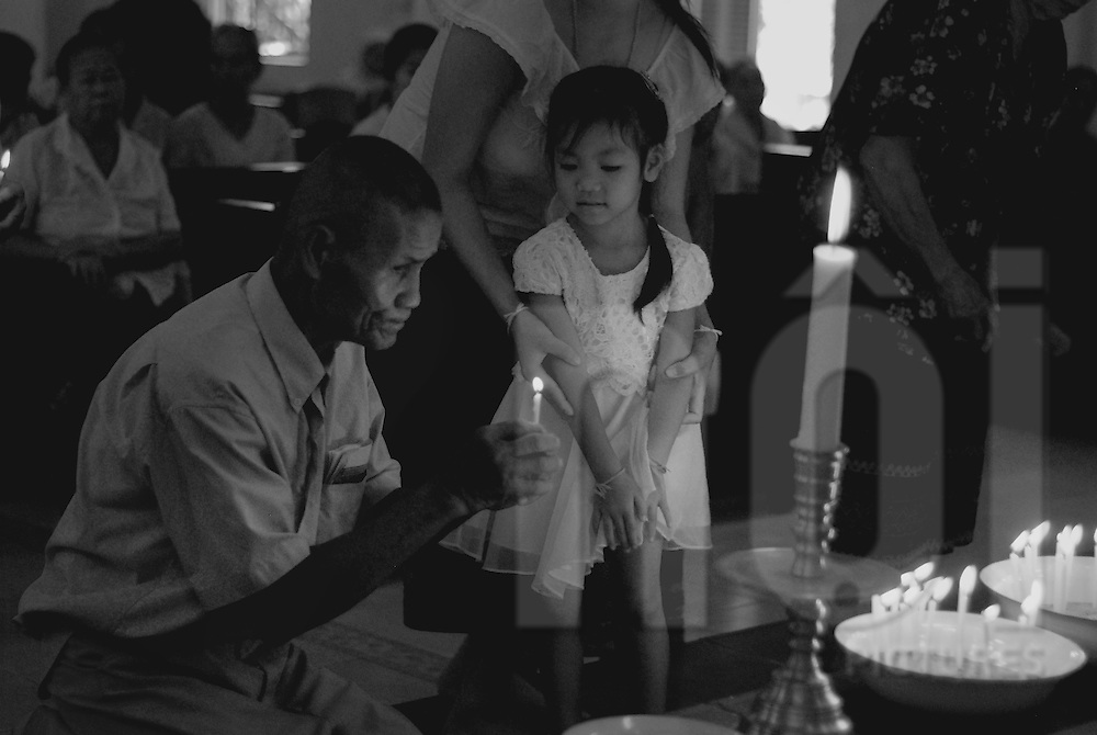 a man lights a candle in a church of Vientiane, Laos, Asia. A little stands in the arms of her mother and look at the flame.