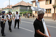 """A member of Florin Cioaba's family carries the cross for his grave. The route from Florin Cioba's home to the cemetery - there are crowds of people. Many people, onlookers Gypsy and not line the streets, watching from windows and the pavement. The hearse is surrounded by security.<br /><br />Florin Ciaoba's funeral and the crowning of two kings. Daniel and Dorian were crowned, Danile with the bigger crown is King of Romanian Roma Gypies whilst his older Brother Dorian has the smaller crown and is King of Gypsies of the world and deals with foriegn affairs. His hearse (a lorry) packed with security guards is taken from The Cioaba family home to the cemetery<br /><br />Florin Tănase Cioabă (1954 – 18 August 2013) was a Romanian Romani Pentecostal minister and self-proclaimed """"King of Roma around the world"""". He died on 18 August 2013 of cardiac arrest at Akdeniz Üniversitesi in Antalya. He was 58 years old.<br /><br />In September 2003, Florin Cioaba sparked controversy when he married his 12 year-old daughter Ana-Maria to Mihai Bitrita, a Roma boy aged 15. However, following the wave of criticism, he promised to work to uproot the tradition of child marriages among the Roma. Florin Cioaba also encouraged Roma families to send their children to school during his attempt to fight poverty resulting from a lack of education.<br /><br />Cioaba was elected president of the International Romani Union in April this year"""