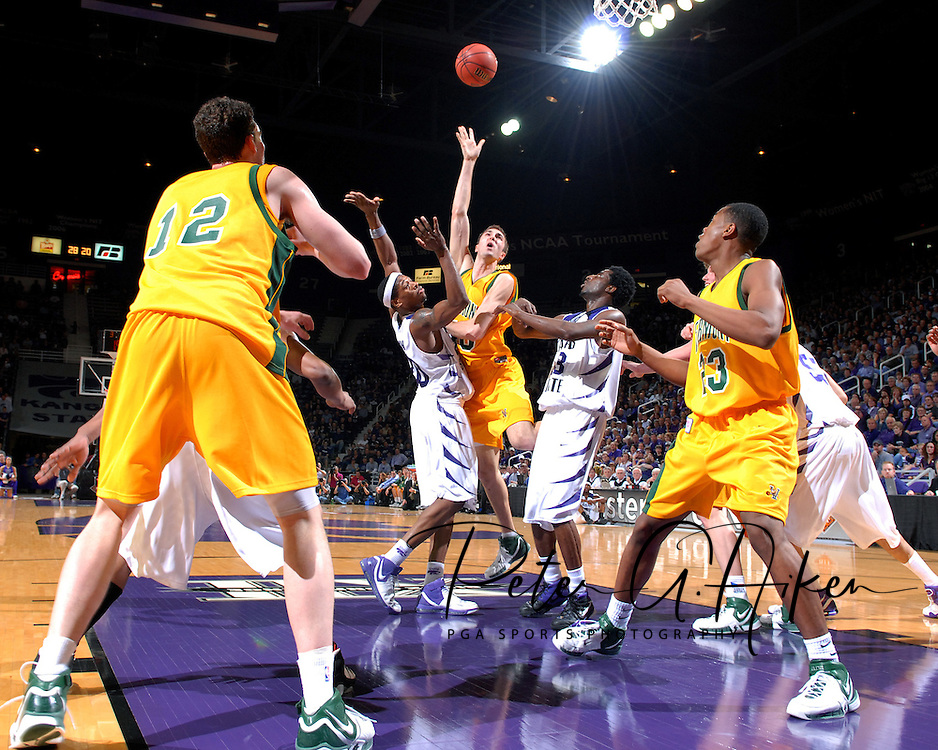 Vermont forward Colin McIntosh (40) puts up a shot in the lane over Kansas State defenders Cartier Martin (20) and Jermaine Maybank (23), as Catamount teammates Marqus Blakely (23) and Joe Trapani (12) look on during first half action at Bramlage Coliseum in Manhattan, Kansas, March 14, 2007.  Kansas State defeated Vermont in the first round of the NIT 59-57.