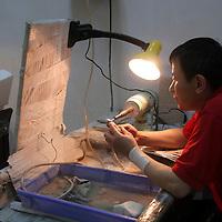 Asia, China, Shaanxi, Xian. A craftsman carves jade at the Jade Factory in Xian.