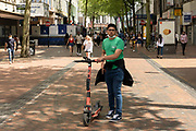 Young man on an eScooter slowly and responsibly passes shoppers on New Street on 14th June 2021 in Birmingham, United Kingdom. eScooters, or electric scooters are becomming a controversial sight on our streets and pavements with the speedy scooters linked to accidents and anti-social behaviour.