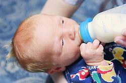 Newborn baby drinking milk from bottle,