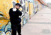 Portrait of a urban rapper near a wall