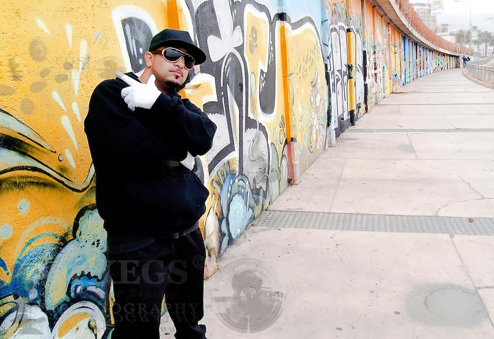 Portrait of a urban rapper near a wall