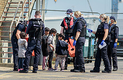 © Licensed to London News Pictures. 20/07/2021. Dover, UK. Young migrants are escorted by Border Force officers as they are brought ashore at Dover Harbour in Kent after crossing the English Channel. It is being reported that at least 430 migrants crossed the English Channel to the UK on Monday, a new single day record. Photo credit: Stuart Brock/LNP