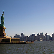 The Statue of Liberty stands tall as visitors take a boat tour of the famous landmark.