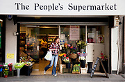 Woman leaving The People's Supermarket. The Peoples Supermarket is a community and membership based scheme to make food more accessible and cheaper for those who use the project. Anyone can join the scheme and all they have to do is work in the shop for a few hours a month, in return for a percentage off their shopping bill.