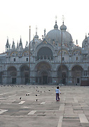 Child playing at dawn in the Piazza San Marco, Venice, Italy