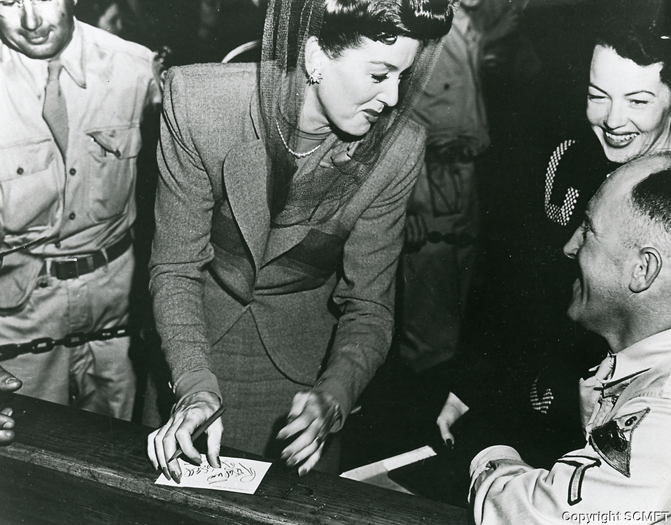 10/3/42 Rosalind Russell signs autographs during the Hollywood Canteen's grand opening.