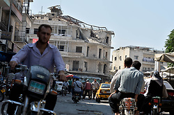 A Syrian people use transportation in front of destroyed building was hit by a reported air strike by Russian air force in the district of Jisr al-Shughur, in the Idlib province. Syria, September 11, 2018. Photo by Ugur Can/DHA/ABACAPRESS.COM
