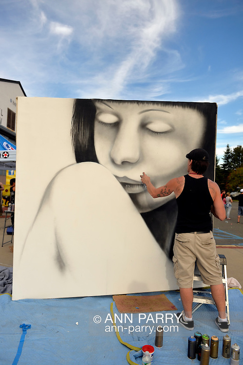 Garden City, New York, USA. 14th September 2014. SEAN GRIFFEN, aka NME, of Freeport, is a graffiti artist creating an outdoor mural of a girl, at the United Ink Flight 914 tattoo convention at the Cradle of Aviation museum of Long Island.