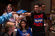A guest gestures for a Hilary Clinton poster during the Dallas County Democratic watch party in Dallas, Texas on November 8, 2016. (Cooper Neill for The Texas Tribune)