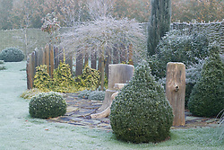 Seating area with rustic table and chair. Topiary of clipped box. Slate pillars used as screen.  Frosty winter's morning. Design: John Massey, Ashwood Nurseries
