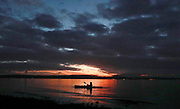 A kayaker watches the sun set at Lowman Beach Park in Seattle. (Erika Schultz / The Seattle Times)