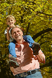Father carrying son on shoulders, smiling, Bavaria, Germany