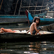 Young girl in wooden canoe amidst wooden fishing village houses (Siem Reap, Cambodia - Oct. 2008) (Image ID: 081023-1632561a)